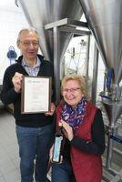 Marion Hoch und Wilfried Reiners vor der Sedimentationsanlage der Rapsölproduktion mit dem Zertifikat