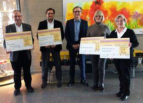 Bei der Spendenübergabe halten die Spendenempfänger einen großen symbolischen Scheck in die Höhe